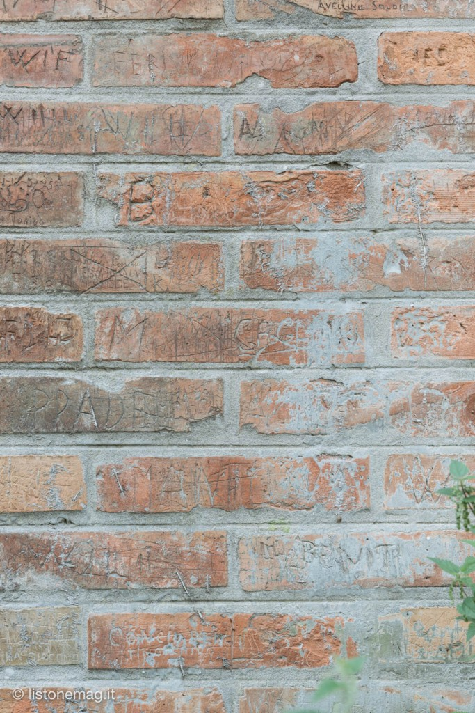 I nomi incisi nei muri vicino all'ingresso di via Scandiana
